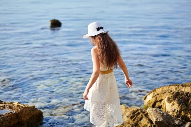 Uma jovem com um vestido e chapéu branco caminha ao longo de uma praia de pedras perto do mar