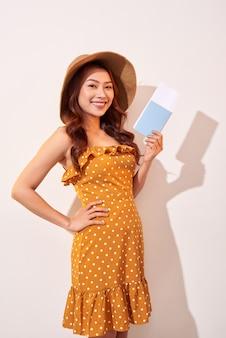 Uma jovem com um vestido laranja de bolinhas e um chapéu de palha na cabeça está segurando um passaporte e passagens de avião