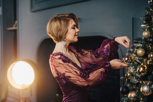 Uma jovem com um vestido luxuoso está perto de uma árvore de natal e tem uma bola decorativa nas mãos