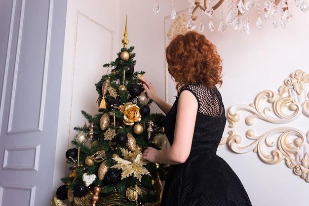 Uma jovem com um vestido preto festivo decora a árvore de natal com brinquedos dourados e pretos