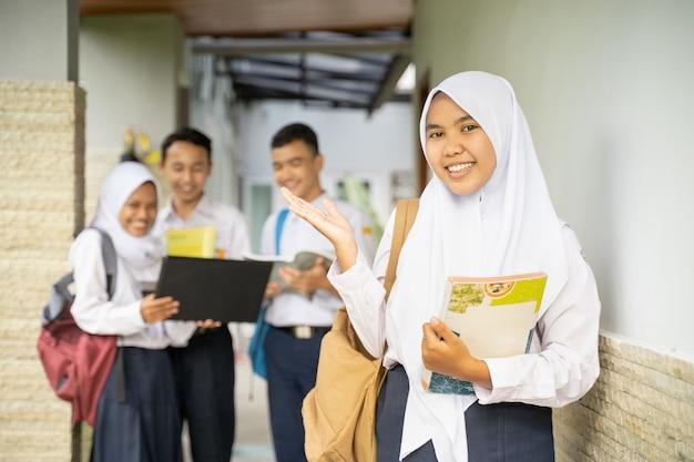 Uma jovem com um véu sorri para a câmera com gestos com as mãos em um uniforme escolar carregando uma escola ...