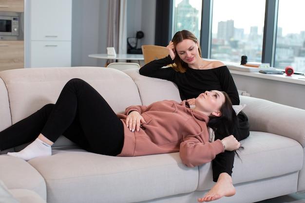 Uma jovem com uma blusa rosa colocou a cabeça de sua amiga sobre os joelhos enquanto estava deitada em um sofá bege em casa. foto de alta qualidade