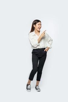 Uma jovem com uma camisa branca e apontando para cima
