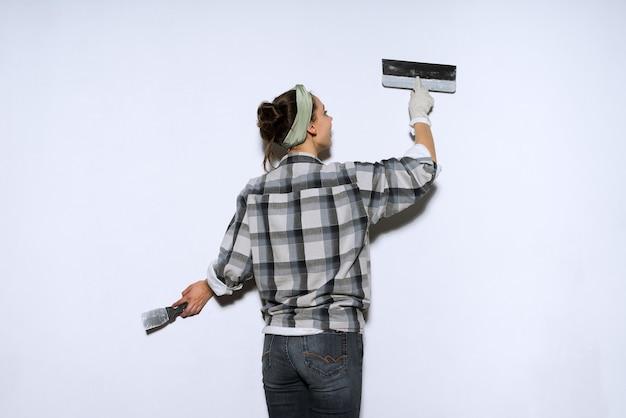 Uma jovem com uma camisa xadrez fazendo reparos em seu novo apartamento, nivelando as paredes com uma espátula
