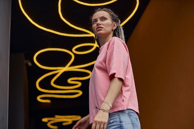 Uma jovem com uma camiseta rosa está de pé contra o fundo de um teto de néon amarelo e olha para cima ...