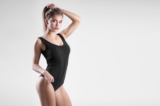 Uma jovem com uma figura esportiva em um corpo negro sobre fundo branco