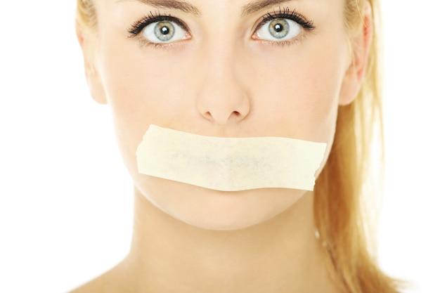 Uma jovem com uma fita na boca sobre um fundo branco