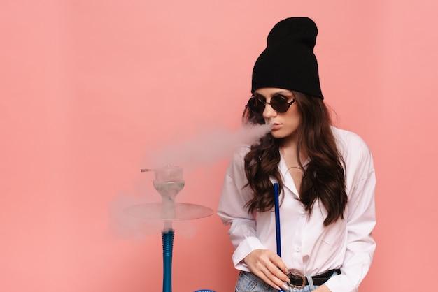 Uma jovem com uma imagem de hipster fuma cachimbo de água, sheesha e gosta de fumar.