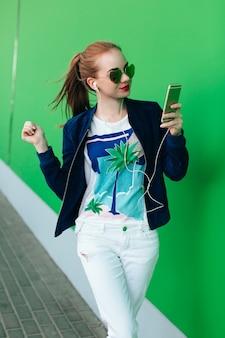 Uma jovem com uma jaqueta azul e calça branca está em pé ao ar livre perto de uma parede verde com linha branca para baixo. a garota usa óculos escuros com corações. ela está diminuindo a música com a ajuda de fones de ouvido.