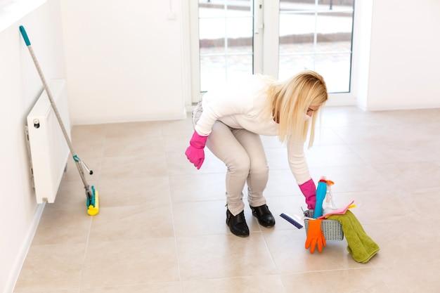 Uma jovem com uma máscara e luvas segura um frasco de spray nas mãos. arte conceitual para limpeza de salas e prevenção de doenças virais.