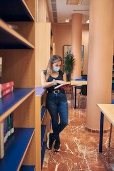 Uma jovem com uma máscara está na biblioteca olhando um livro