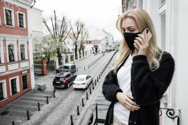 Uma jovem com uma máscara preta está de pé na varanda do escritório e falando ao telefone