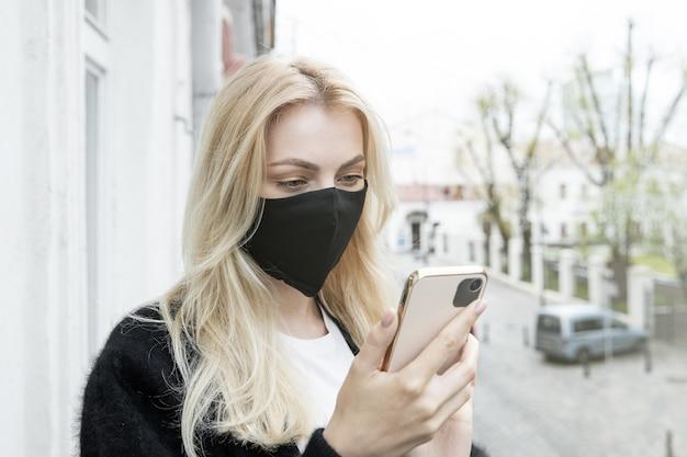Uma jovem com uma máscara preta está de pé na varanda do escritório e mandando mensagens de texto ao telefone