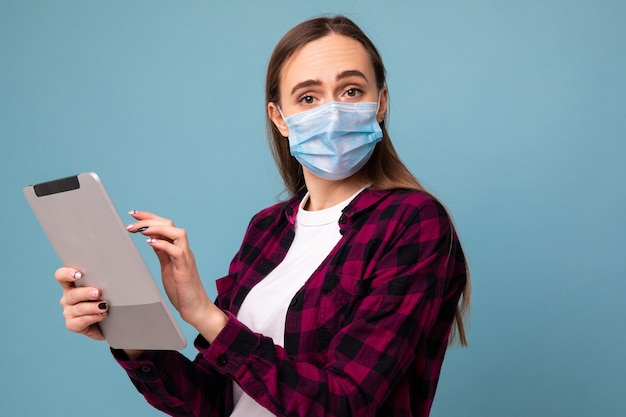 Uma jovem com uma máscara protetora digita em um tablet em um fundo azul
