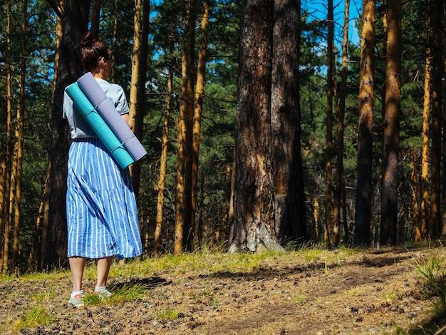 Uma jovem com uma saia leve caminha pela floresta e carrega esteiras de ioga nas costas, copyspace,