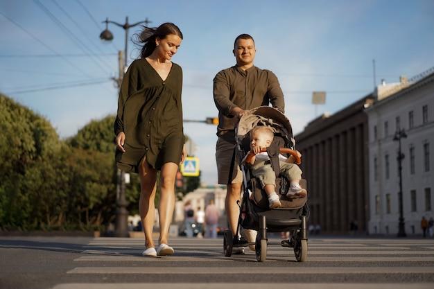 Uma jovem com vestido de cor cáqui e seu marido atravessando a rua na passadeira com o
