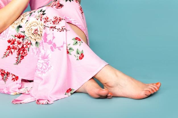 Uma jovem com vista de frente em um vestido rosa de design floral sentada no azul
