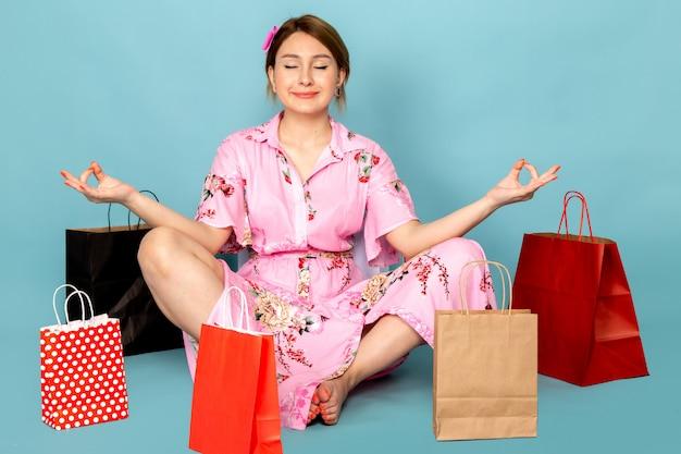 Uma jovem com vista frontal em um vestido rosa de design floral sentada e meditando com um sorriso e pacotes de compras em azul