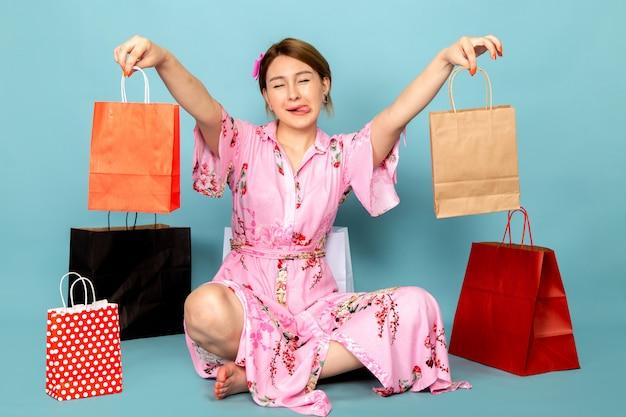 Uma jovem com vista frontal em um vestido rosa de design floral sentada e posando com um sorriso e pacotes de compras em azul