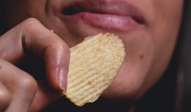 Uma jovem comendo uma batata frita em macro fotografia