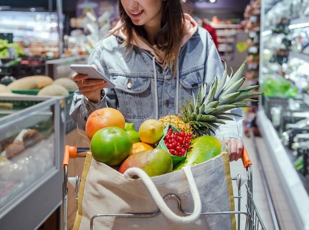 Uma jovem compra mantimentos em um supermercado com um telefone nas mãos.