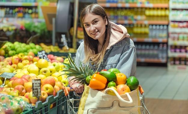 Uma jovem compra mantimentos em um supermercado.