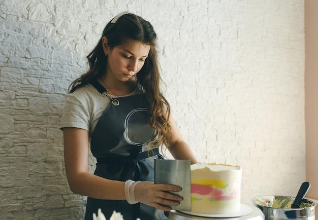 Uma jovem confeiteira com um avental cinza decora um bolo na cozinha.