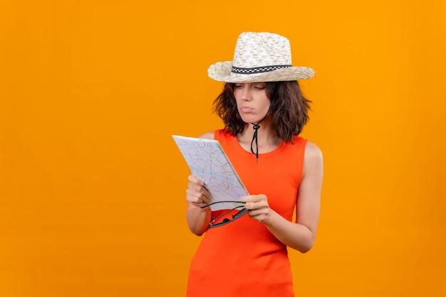 Uma jovem confusa, com cabelo curto e uma camisa laranja, usando um chapéu de sol segurando óculos de sol, olhando para o mapa