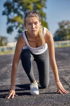 Uma jovem corredora se preparando para uma corrida na pista