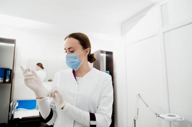 Uma jovem cosmetologista branca se prepara para examinar seus pacientes.