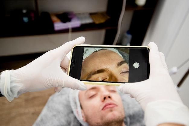 Uma jovem cosmetologista está tirando uma foto de seu cliente para compartilhar o resultado com outras pessoas nas redes sociais.
