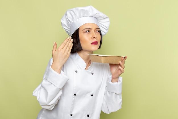 Uma jovem cozinheira de frente para a cozinha com terno branco e boné segurando uma tigela na parede verde
