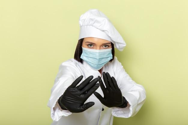 Uma jovem cozinheira de frente para a cozinha com terno branco e boné usando luvas e máscara esterilizada com pose cautelosa na parede verde.