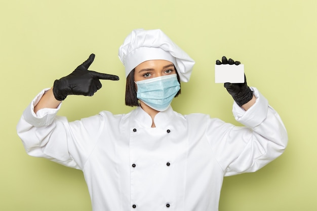 Uma jovem cozinheira de frente para a cozinha com terno branco e boné usando luvas e máscara na parede verde senhora trabalha comida culinária cor