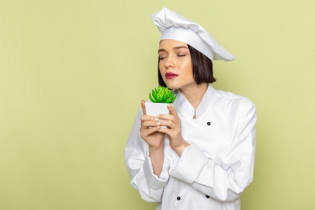 Uma jovem cozinheira de frente para a cozinheira de terno branco e boné segurando e cheirando a planta verde na parede verde