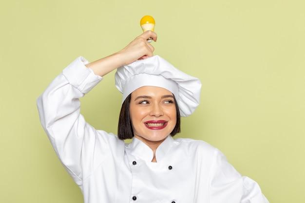 Uma jovem cozinheira de frente para a cozinheira de terno branco e boné segurando uma lâmpada amarela na parede verde senhora trabalhar comida culinária cor