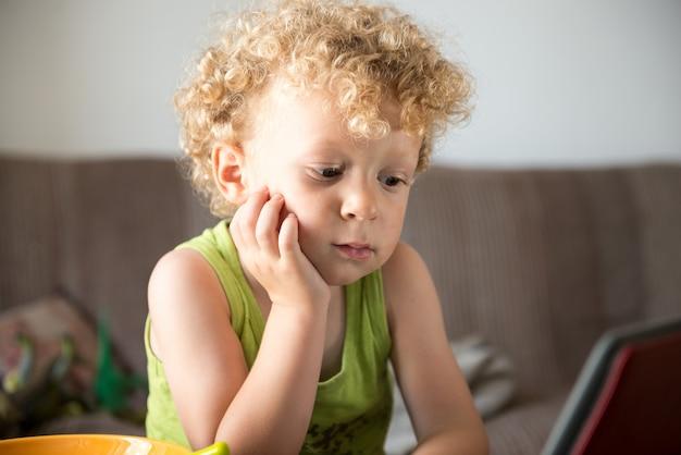 Uma jovem criança loira parece um tablet
