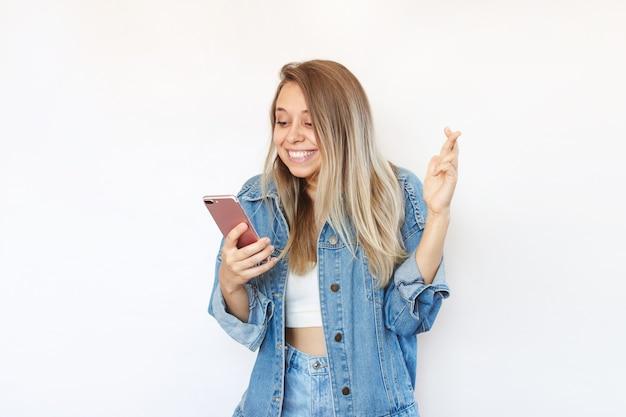 Uma jovem cruza os dedos para dar sorte olhando para a tela do telefone esperando o resultado dos exames