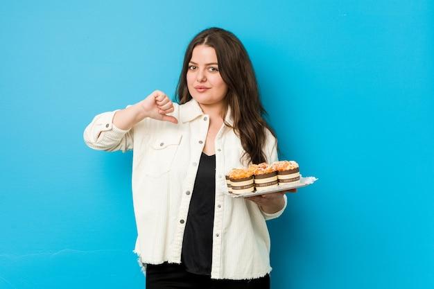 Uma jovem curvilínea segurando um cupcakes sente-se orgulhosa e autoconfiante, exemplo a seguir.
