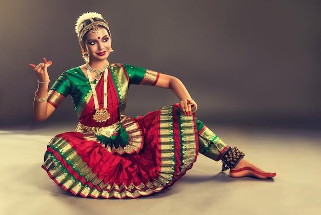 Uma jovem dançarina de dança clássica indiana vestida com um traje tradicional está demonstrando uma das poses