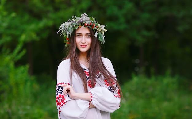 Uma jovem de aparência eslava com uma coroa de flores silvestres no meio do verão.