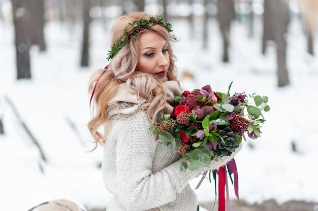 Uma jovem de aparência eslava com uma coroa de flores silvestres. noiva loira linda detém um buquê em plano de inverno.