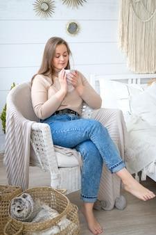Uma jovem de aparência européia senta-se em uma cadeira e bebe chá com um sorriso no rosto