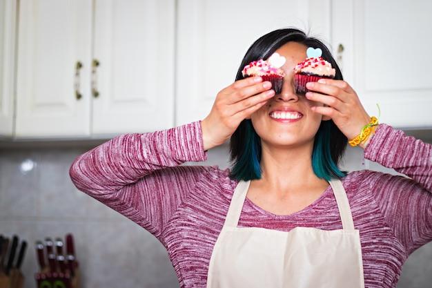 Uma jovem de avental na cozinha, sorrindo e segurando dois cupcakes
