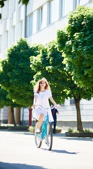Uma jovem de bicicleta azul anda sozinha pela rua da cidade