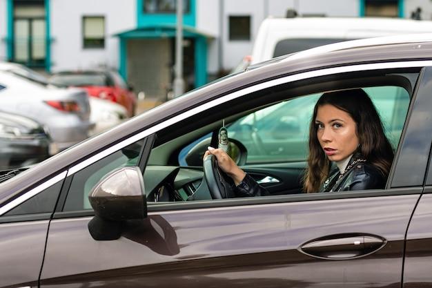 Uma jovem de cabelo comprido está sentada ao volante de um carro e olhando pela janela