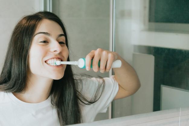 Uma jovem de cabelos pretos escovando os dentes com uma escova elétrica