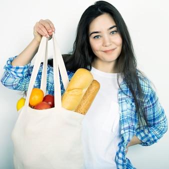 Uma jovem de camisa azul segura uma sacola de tecido com comida