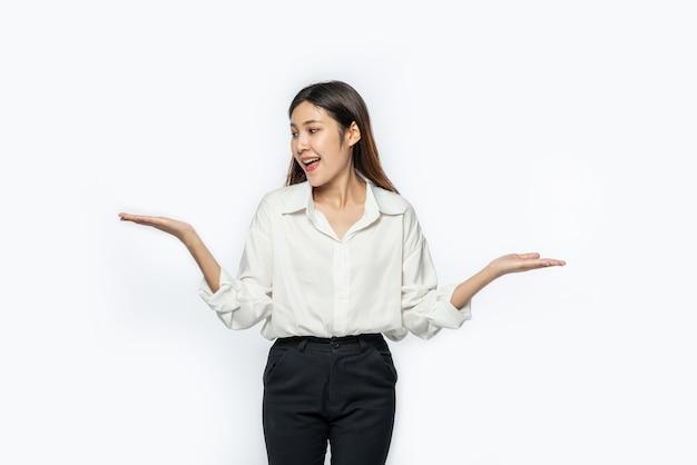 Uma jovem de camisa branca com as duas mãos abertas