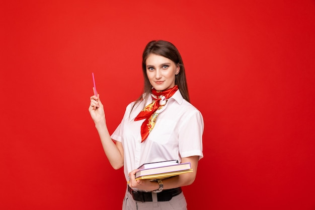 Uma jovem de camisa branca com diários em uma parede vermelha
